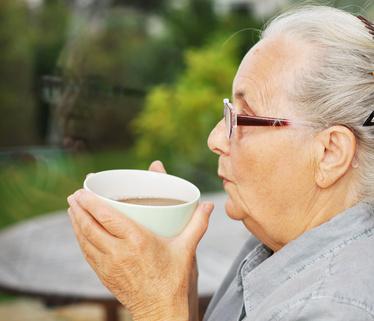 Ältere Dame trinkt Kaffee